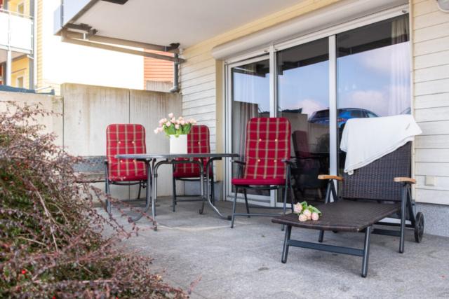 Terrasse mit Stühlen, Tisch und Liegen